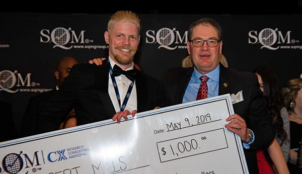 Two men, an award recipient wearing a tuxedo and the award presenter wearing a suit, holding an over-sized prize money cheque for $1,000.