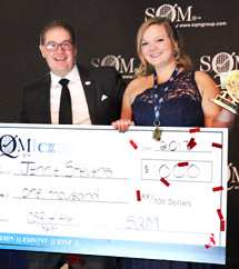 A woman and a man smiling, the woman an award recipient wearing a dress and the man the award presenter wearing a suit, both holding an over-sized prize money cheque for $1,000.