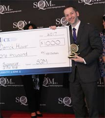 A man with a big smile standing on a presentation stand, who is wearing a suit, holding an over-sized prize money cheque for $1,000.